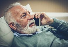 I learned something new. Senior man lying on bed and talking on smart phone. Close up stock photo