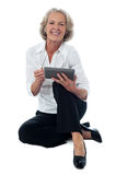 I am learning to use this device. Seated elderly woman operating digital tablet Stock Photos
