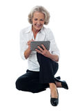 I am learning to use this device. Seated elderly woman operating digital tablet Royalty Free Stock Photos