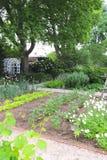 I letti di fiore misurati e la piantatura metodica si dirigono verso un bello orto e del fiore fotografia stock