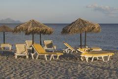 I letti e gli ombrelli del sole dell'estate sulla Grecia sabbiosa tirano alla sera Spiaggia con i parasoli Fotografia Stock Libera da Diritti