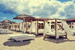 I letti e i sunloungers in una spiaggia bastonano in Ibiza, Spagna Fotografia Stock