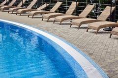 I lettini vuoti del rattan del Poolside dell'hotel si avvicinano allo scrutinio di nuoto Immagini Stock