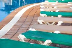 I lettini vuoti del rattan del Poolside dell'hotel si avvicinano allo scrutinio di nuoto con Crystal Clear Water And Concrete blu Immagine Stock Libera da Diritti