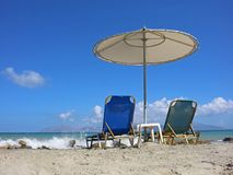 I lettini vuoti sulla spiaggia con la spruzzatura ondeggia Immagini Stock Libere da Diritti