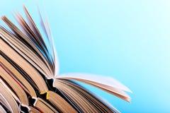 I libri aperti sono impilati sullo scrittorio, su un fondo blu Compito difficile a scuola, una montagna di conoscenza fotografia stock
