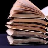 I libri aperti sono impilati sullo scrittorio, su un fondo nero, isolato Compito difficile a scuola, una montagna di conoscenza fotografia stock libera da diritti