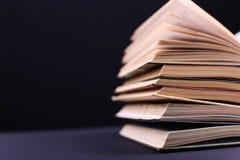 I libri aperti sono impilati sullo scrittorio, su un fondo nero, isolato Compito difficile a scuola, una montagna di conoscenza immagine stock