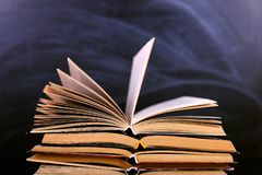 I libri aperti sono una pila sullo scrittorio, contro lo sfondo di un bordo di gesso Compito difficile a scuola, una montagna di  immagini stock libere da diritti