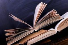 I libri aperti sono una pila sullo scrittorio, contro lo sfondo di un bordo di gesso Compito difficile a scuola, una montagna di  fotografie stock libere da diritti