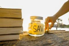 I libri e le monete disposti sul pavimento di legno, risparmiano i soldi per preparano in futuro Risparmio di concetto per l'istr Immagine Stock Libera da Diritti