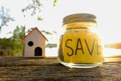 I libri e le monete disposti sul pavimento di legno, risparmiano i soldi per preparano in futuro Risparmio di concetto per l'istr Immagine Stock