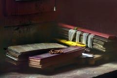 I libri sacri di preghiera tibetana, legati con i nastri gialli, si trovano accanto alla parete di pietra marrone rossiccio Immagini Stock Libere da Diritti