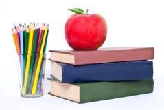 I libri torreggiano su con la mela Immagine Stock