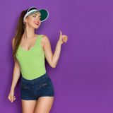 I Like It. Beautiful young woman in lime green shirt, sun visor and jeans shorts showing thumb up, looking over shoulder at copy space and smiling. Three quarter Royalty Free Stock Image