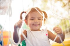 I like days in the playground. Little happy girl spending time on playground. Close up. Space for copy royalty free stock photography