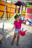 I like fun in the sand. Little girl playing with sand in playground royalty free stock photography