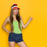 I Like It. Happy young woman in red sun visor, jeans shorts and lime green shirt showing thumb up. Three quarter length studio shot on yellow background Royalty Free Stock Image