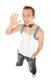 I like music and tell you hello. Smiling handsome young man in casual style with headphones shows hello by his hand, isolated on white background Royalty Free Stock Photography