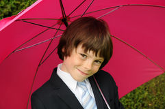 I like pink too. Cute little boy dressed like a businessman with s pink umbrella Royalty Free Stock Photos
