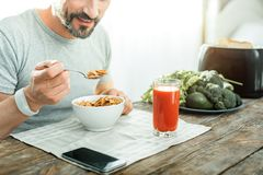 Satisfied unshaken man eating cereals and holding a spoon. I like it. Satisfied unshaken happy man sitting by the table eating cereals and holding a spoon Stock Photography