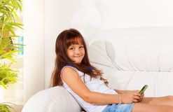 I like sending messages. Happy shy smiling little girl with cell phone text her friends Royalty Free Stock Photography
