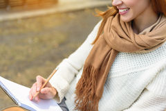 I like to draw nature. Creative young woman is drawing in park with pleasure. She is sitting and laughing Royalty Free Stock Image
