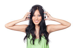 I like what I hear. A young Asian girl listening to music with her hands grasping the headphones Stock Image