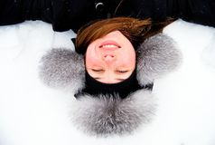 I like winter!. Beautiful girl in fur hat lying in the snow upside down Stock Image