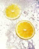 I limoni sono caduto nell'acqua Immagine Stock