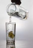I limoni sono caduto in un vetro con acqua Fotografia Stock