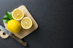 I limoni sono sopra il tagliere di legno con il coltello Fotografia Stock
