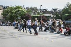 I-linje skateboradåkare som utför för en folkmassa, Paris, Frankrike Arkivbilder