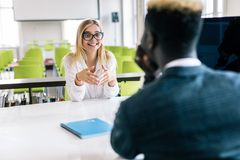I listen to your suggestions. Portrait of confident qualified young afro american manager is sitting with his colleague female at royalty free stock photos