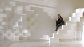 I ljust studioung flickasammanträde på trappa och samtal vid den videopd appellen på minnestavlan lager videofilmer