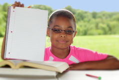 I'll Be Happy To Display A Message. Young girl holds a notebook with blank space to display your message or reminder to students.  Short depth of field with Royalty Free Stock Images