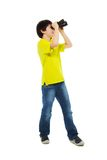 I'll find alll I need. Happy boy holding binoculars and smiling, isolated on white, side view, full height Stock Photos