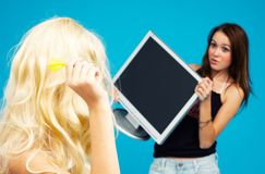 I'll get you. Girl about to hurl a dart at another girl who is trying to shield herself with a LCD panel Royalty Free Stock Images