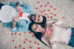I`ll give you my heart! Man decided to show his feelings!  Top v. Iew photo of excited cheerful lovely cute beautiful lovers holding heart cards in hands, lying Royalty Free Stock Image