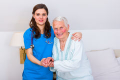 I`ll have to learn to walk again. Elderly patient starting to wal, a beautiful brunette geriatric doctor helping her first steps Royalty Free Stock Image