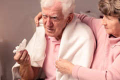 I'll help you in sickness. Senior women supporting her ill, sad husband Stock Photography