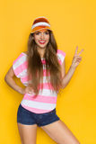 I'll Take Two. Smiling young woman in pink stripped shirt, jeans shorts and orange sun visor posing with hand on hip and showing two finger or peace sign. Three Royalty Free Stock Photography