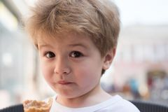 I look nice and so my hair does. Small boy with stylish haircut. Little child with short blond hair. Little child eating. Outdoor. Healthy hair care habits royalty free stock photography