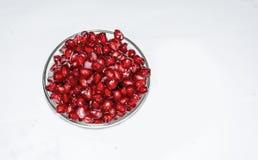 I lotti del melograno maturo succoso semina su una ciotola di vetro con fondo bianco fotografia stock