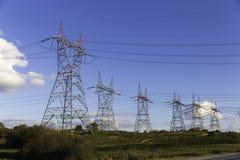 I lotti del trasporto di energia ad alta tensione si eleva con il fondo del cielo blu Immagini Stock