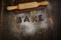 Love bake concept. I love bake concept. Rolling pin, kitchen towel and flour on wooden table royalty free stock photos