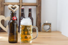 I love beer concept. With a heart shaped cutout around the neck of a beer bottle alongside a full tankard Royalty Free Stock Photos