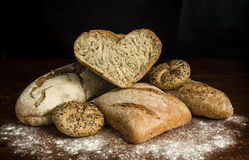 I love Bread. Diffrent kinds of bread and a heart shaped one  on wooden table , you can expand  up and add text Stock Photo