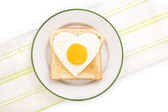I love breakfast. Fried egg sunnyside in heart shape on plate, top view. I love breakfast. Fresh modern image language. Culinary arts royalty free stock photography