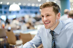 I love this cafe environment. Relaxed smiling corporate male sitting in restaurant stock photo